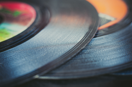 grooves: Single record section extreme close up, black grooves detail and colorful defocused label