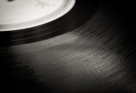 grooves: Lp record section extreme close up, black and white grooves detail and defocused label