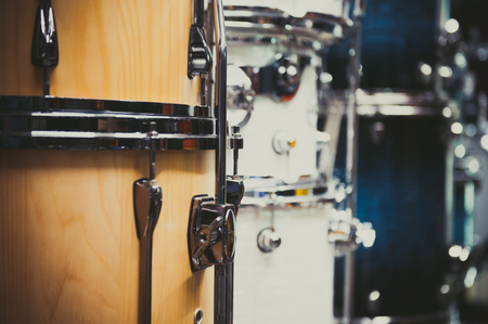 drum and bass: Wooden bass drum detail with different drums aligned in store, selective focus