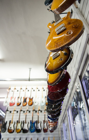 gibson: Rome, Italy. September 20th 2016.  Gibson Les Paul electric guitars hanging in store, with out of focus Fender style guitars in background Editorial