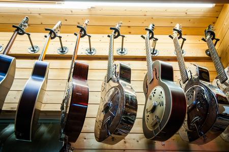 resonator: Rome, Italy. September 20th 2016.  Dobro guitars collection, rare different colors aligned hanging in store Editorial