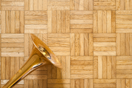 wind instrument: Trombone bell on brown wooden parquet, wind instrument jazz music symbol and copy space