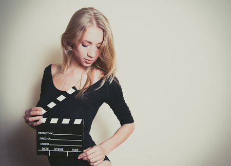 audition: Young blonde woman actress in black shirt posing for audition with movie clapper board Stock Photo