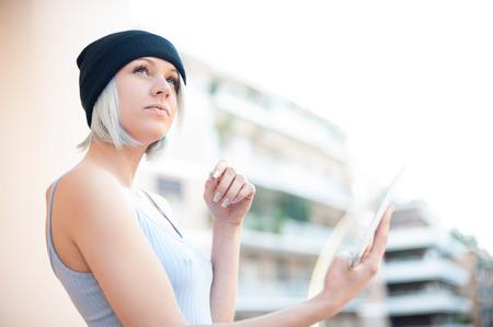 autonomia: inconformista muchacha joven y bonita con la tablilla de mira para arriba en el cielo pensando en la escritura