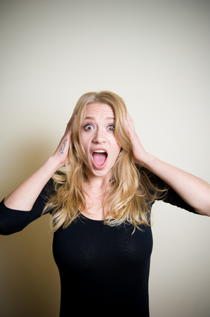 stunned: Young beautiful blonde woman astonished stunned portrait, hands on head and open mouth Stock Photo