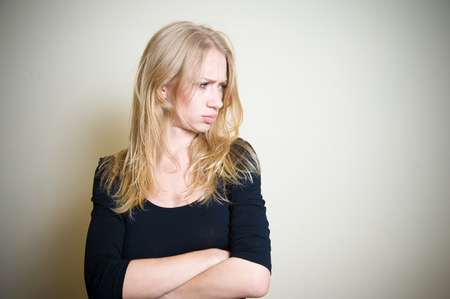 sullen: Young blonde attractive woman looking on her side, face expression angry, sullen, sulky, offended, peevish, clear wall in background Stock Photo