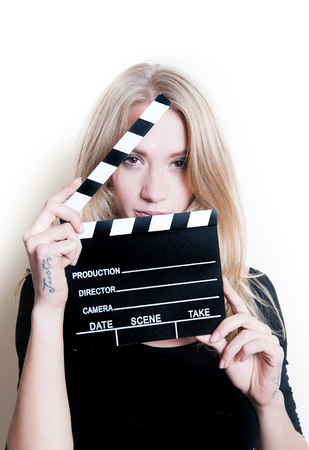 audition: Young blonde woman actress in black shirt posing for audition with movie clapper board, looking at camera