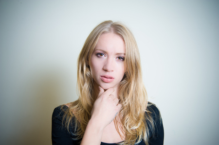 Young blonde woman thoughtful looking at camera, portrait