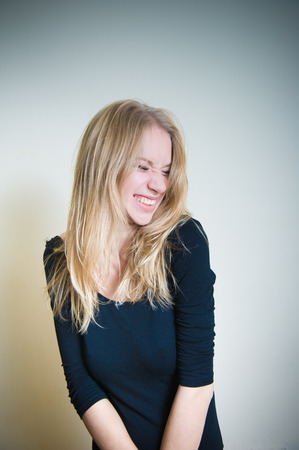 smirking: Young blonde woman, smirking with little grimace on white background