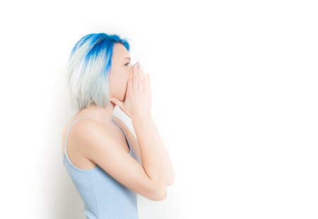 exaggerated: Young teen woman hipster style and blue hair profile screaming with hands on face, isolated on white Stock Photo