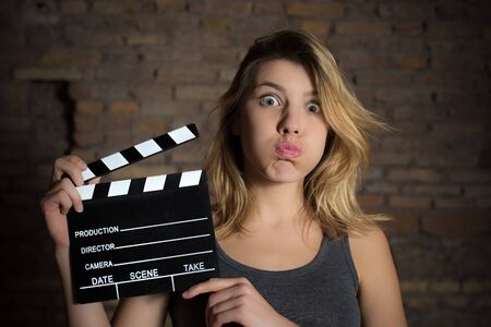 audition: Young blonde girl grimace face and posing with movie clapper board for actress audition