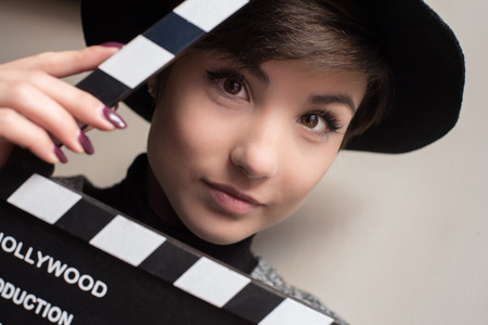 audition: Young woman portrait, actress holding movie clapper behind her face Stock Photo