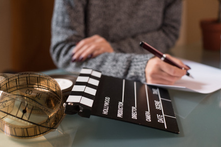 Artist screenwriter desktop detail with movie clapper board and filmstrip with womans hand working in background Stock Photo