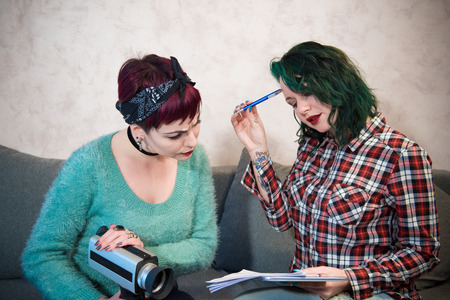 Couple of young filmmaker women sitting at home collaborating working and about movie idea, pen paper and vintage movie camera Stock Photo