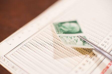 Tweezers put old postal stamp on perforation gauge for measurement