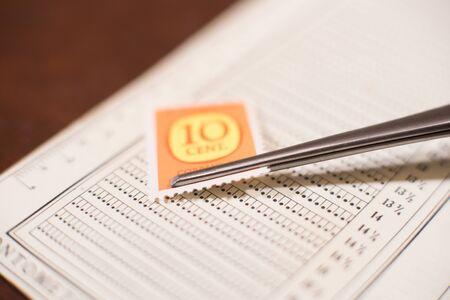 postal stamp: Tweezers put old postal stamp on perforation gauge for measurement