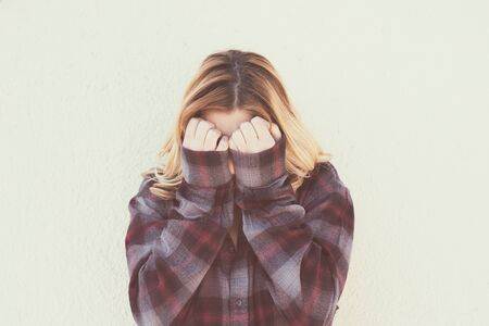 bashfulness: Young woman with hands over face in retro style portrait concept of fear shame and shyness, vintage retro color effect style Stock Photo