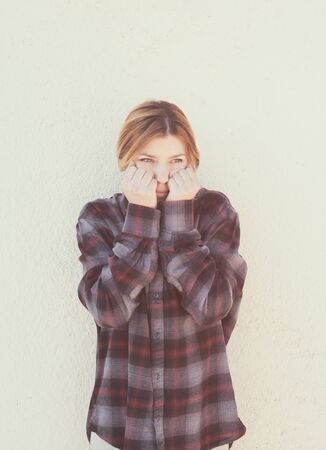 bashfulness: Young woman with hands over face in retro style portrait concept of shame and shyness, vertical vintage retro color effect style