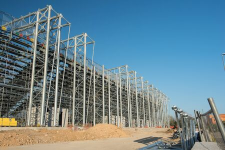 Frosinone, Italy april 23 2017: External view of footbal stadium under construction with steel structure, bleachers and colorful seats on blue sky Editorial