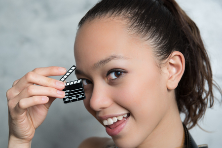 audition: Young pretty woman smiling portrait with movie clapper board near her face