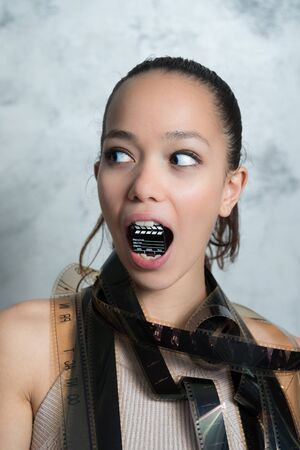 audition: Young pretty woman funny portrait with movie filmstrip and little clapper board in her mouth