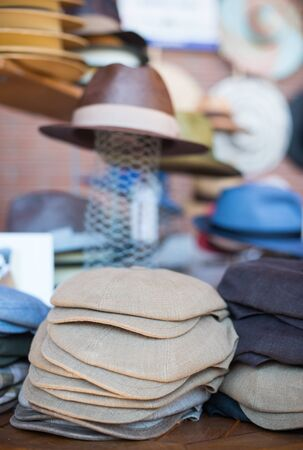 newsboy cap: Market stall full of different hats, flat cap heap in foreground Stock Photo