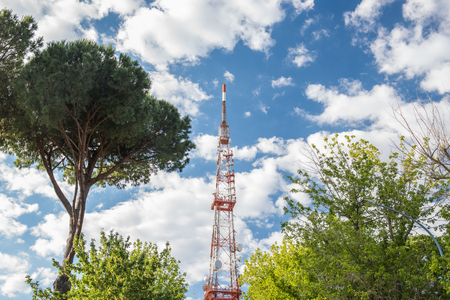 High network telecommunication tower and green trees aerial over blue cloudy sky Stock Photo