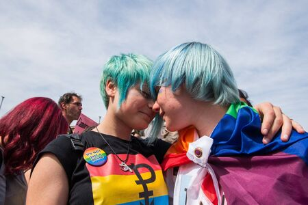 sexual orientation: Rome, Italy june 10th 2017. Colorful lesbian couple with rainbow flag kissing on the street during gay pride parade Editorial