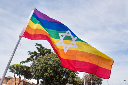 Colorful rainbow peace flag with star of david hexagon symbol over sky