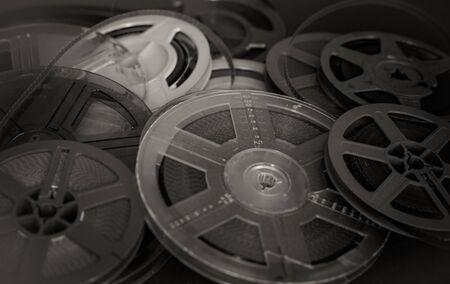 evocative: Heap of aged vintage super 8 mm movie reels, black and white selective focus detail