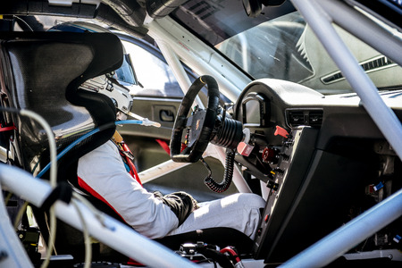 Vallelunga, Rome, Italy. June 24 2017. Porsche Carrera racing car cockpit interior view with driver before race, instrument panel steering wheel  dashboard and driver seat with safety equipment