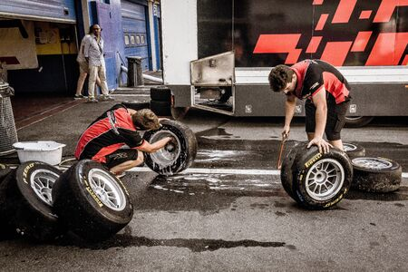 Vallelunga, Rome, Italy. June 24 2017. Couple of mechanics working in circuit pit cleaning and washing racing tires set
