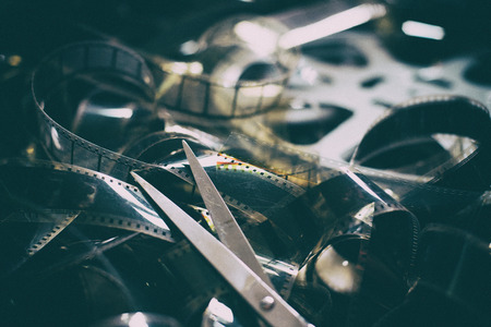 Vintage movie in cinematic color effect, unrolled 35mm filmstrip and scissors concept of editing final cut