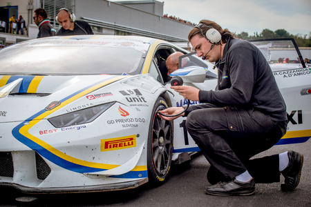 tire tracks: Vallelunga, Italy september 24 2017. Lamborghini huracan and mechanics on starting grid, man checking tire pressure before the race Editorial