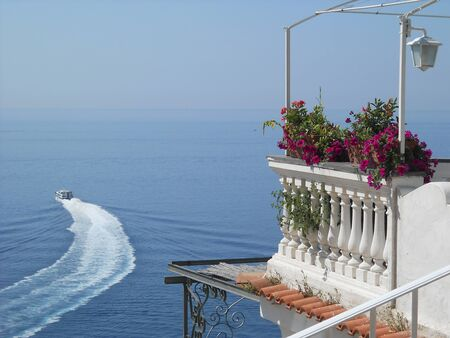 motorboats: Motorboat departs with flowered balcony in the foreground