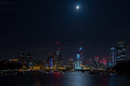 London city skyline at night with full moon