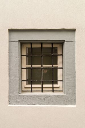 Window with iron grating and white wall
