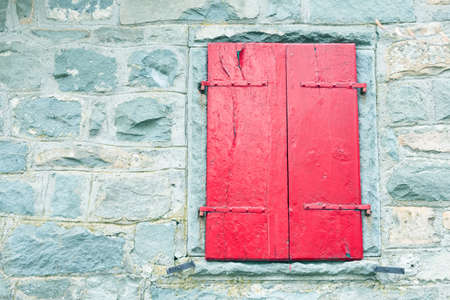 red shutters: red shutters of an old window on a stone wall