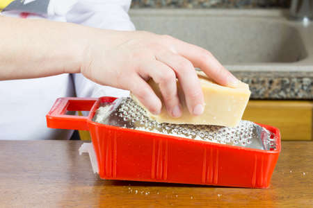 girl grating a piece of Parmesan cheese Stock Photo