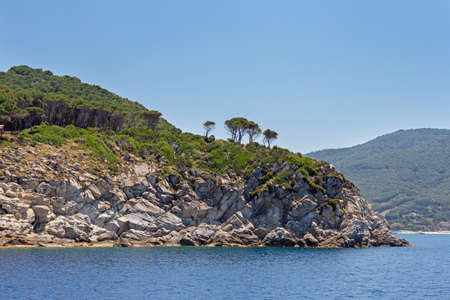 evergreen trees dominate on the cliffs of the island Stock Photo