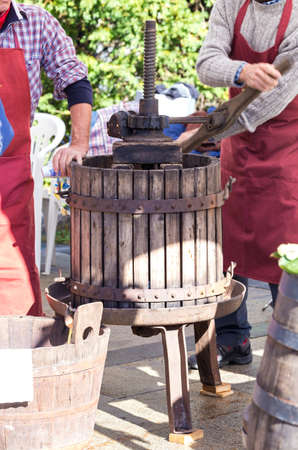 People squeeze the grapes with an old wooden press