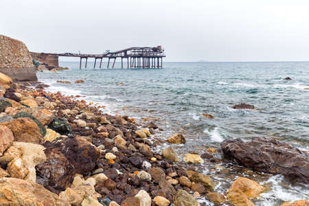 old pier on the rocks of the coast