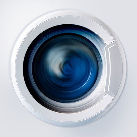 Front view and portion of the porthole of the washing machine during washing and rotation of the drum containing clothes blue Foto de archivo
