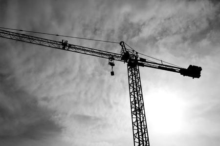 overhead crane: Construction crane bottom view in operation with cloud sky background. BlackWhite photo.