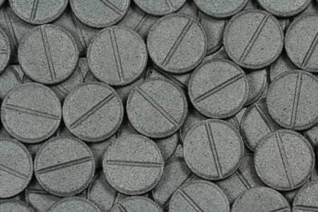 activated: Activated charcoal tablets abstract texture Stock Photo