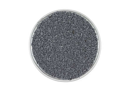 catalyst: black catalyst pellets in a glass container on a white background