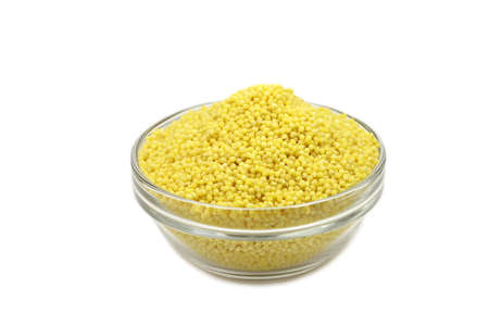 raw millet grains in a glass container on white background