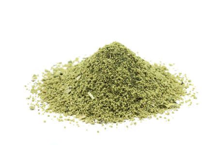 a handful of granulated seasoning green on a white background