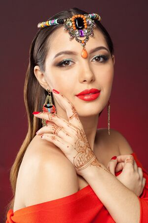color tribal tattoo: beautiful woman in oriental style with mehendi on dark background