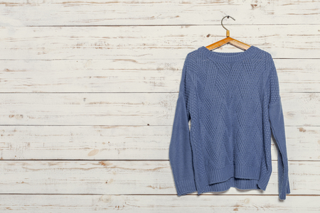 oversize: knitted sweater on wooden clothes rack Stock Photo